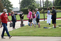 People entering the Benton County Quorum Court committee of the whole meeting Tuesday July 20 2021 walk past sign carriers at Northwest Arkansas Community College where the meeting was held.<br />(NWA Democrat-Gazette/Flip Putthoff)