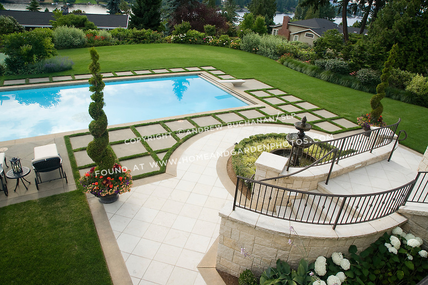 An overhead view looking down a short curved staircase on a beautifully manicured, poolside landscape featuring lush green grass lawn, beds of mixed annuals and perennials, a long beautiful blue swimming pool with built in tiled spa, and matching chaise lounge chairs and dining tables with orange red umbrellas, all with a water view in the short distance behind in this typically Northwest summer scene in a suburban community east of Seattle.