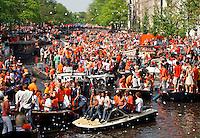 Drukte op de gracht tijdens koningsdag in Amsterdam