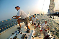 A crew keeps an eye on the horizon as they sail in the evening light on Lake Norman in NC.