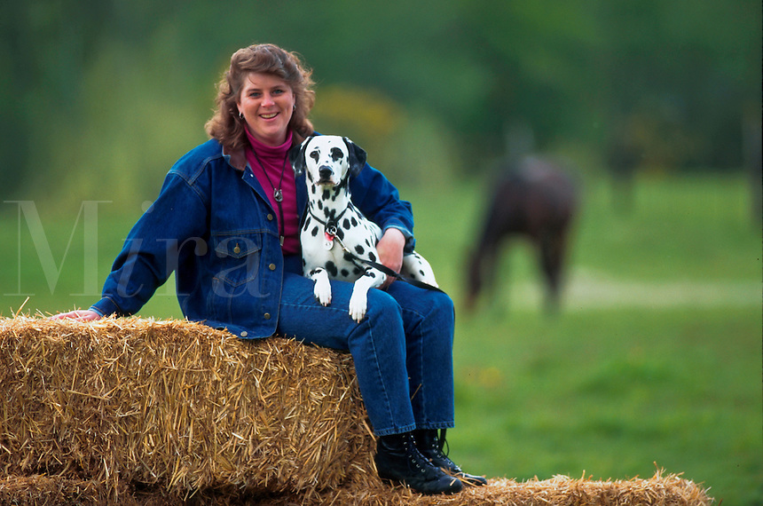 Smiling woman poses on bale of hay while holding her dalmatian.