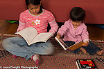imitation modeling 16 month old toddler girl looking at book while 7 year old sister reads nearby