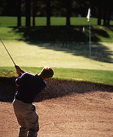 Rear view of a golfer as he hits a ball out of a sandtrap.