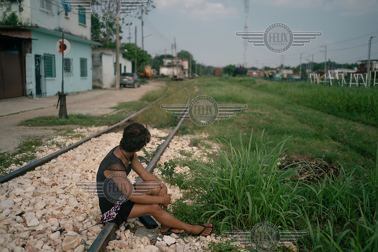 Dulce (16), an unaccompanied Guatemalan migrant, sits on the train tracks where 'La Bestia', or the Beast, passes trough, the train that many migrants have illegally ridden north. Dulce is a transgender woman who left Guatemala for a second time after she suffered from domestic violence in her family and received death threats in her small town.