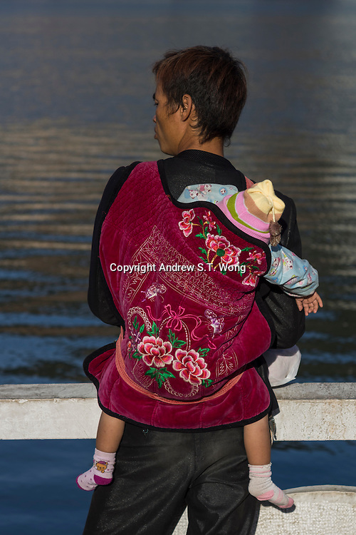 """A man carries his baby as he looks at the lake in Gejiu, November 2014. Gejiu in Yunnan province is a """"Tin Centre"""" with more than 2,000 years of mining history. Tin articles made in Gejiu are highly acclaimed in China. However, the tin mining and related industries are in decline."""