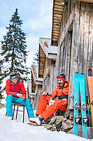 A ski tour through the Pirin Mountains of Bulgaria. A couple sits outside a small cabin at the Demianica Hut with a cat.