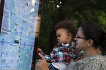 17 month old toddler boy outside with mother pointing at map displayed outside of park
