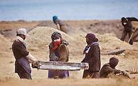 Tibetan farmers use a sifter to separate chaff from grain during the barley harvest