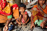 Women and children sift through used electronics in a village near Kolkata.<br />
