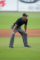 Umpire Ronnie Whiting handles the calls on the bases during the South Atlantic League game between the Hickory Crawdads and the Kannapolis Intimidators at CMC-Northeast Stadium on April 17, 2015 in Kannapolis, North Carolina.  The Crawdads defeated the Intimidators 9-5 in game one of a double-header.  (Brian Westerholt/Four Seam Images)