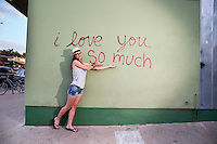 """Attractive local Austin woman poses in front of the famous """"I love you so much"""" mural on South Congress (Soco)."""