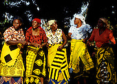 Ujiji, Tanzania. Traditional women dancers with bright coloured printed cotton wrap cloths and headscarves.