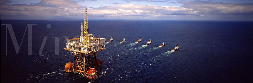 Oil industry. Oil production platform under tow at sea from construction yard to drill site.  Six ocean going tugs. Aerial..