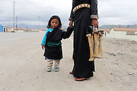A Tibetan hold and his mother in a community on the Tibetan Plateau, in western China. Relocation communities been created to house nomadic herders moved from the highland grasslands. The nomads have been blamed for contributing to the deterioration of the grasslands, so have been moved, sometimes forcibly, into newly built towns that can be found across the plateau.