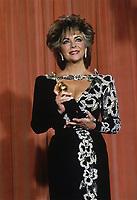 Elizabeth Taylor holding her Golden Globe Award, 1985.
