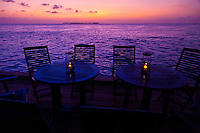 After sunset glow over the sea, deck chairs and tables, on the dock at Wakatobi Dive Resort, Southeast Sulawesi, Indonesia.