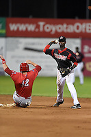 Batavia Muckdogs shortstop Javier Lopez (22) attempts to turn a double play as Rhys Hoskins (12) slides in during a game against the Williamsport Crosscutters on August 26, 2014 at Dwyer Stadium in Batavia, New York.  Williamsport defeated Batavia 8-1.  (Mike Janes/Four Seam Images)
