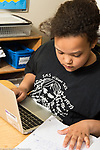5th grade student using laptop computer to research in class