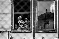Refugees from Bosnia in the Varazdin refugee camp in the winter of 1992. The woman on the left is grandmother 'Nana' with her nephew 'Elvis' (second on the left, first line) and his sister Elvira beside him looking out of the  window of a barrack where they lived as refugees. <br /> <br /> In 1992 while volunteering at the Varazdin refugee camp Panos photographer Bjoern Steinz met and became close to Elvis, a Bosnian Muslim refugee, and his family. They shared the hardships of camp life together which Steinz documented. While the prints were archived for many years two of the images always returned to Bjoern's thoughts. 25 years later he set out to try and find out what had happened to Elvis and his family in the intervening years. Modern social media made the task surprisingly easy and they were reunited in Hadzici where Elvis now lives with his family.