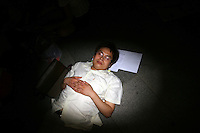 CHINA. Beijing. A man sleeping whilst people around him watch the opening ceremony of the Beijing Summer Olympics. 2008