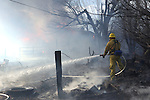 Firefighters battle a 400-acre brush fire in south Reno, Nev., on Friday, Nov. 18, 2011. More than 25 homes have been lost as high winds with gusts up to 60 mph drive the flames. (AP Photo/Cathleen Allison)
