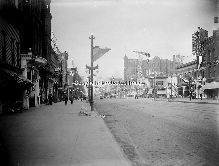 """VIEW WEST ON O STREET, C. 1910. On a typically windy day, O Street--Lincoln's """"Main Street""""--appears to be decked out for the Fourth of July. The camera was positioned on the south sidewalk near Fourteenth Street, looking west. The tall building at the center of the view was the six-story Burr Block, Lincoln's first """"skyscraper,"""" built in 1888.<br /> <br /> Photographs taken on black and white glass negatives by African American photographer(s) John Johnson and Earl McWilliams from 1910 to 1925 in Lincoln, Nebraska. Douglas Keister has 280 5x7 glass negatives taken by these photographers. Larger scans available on request."""