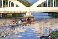 Local men paddling a canoe on Anahulu Stream under the bridge in Haleiwa, O'ahu.