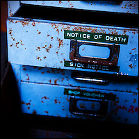 "Rusting metal drawers labelled ""notice of death"" and ""sick notice""."