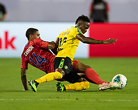 NASHVILLE, TN - JULY 3: Reggie Cannon #14 slides for the ball against Junior Flemmings #12 during a game between Jamaica and USMNT at Nissan Stadium on July 3, 2019 in Nashville, Tennessee.