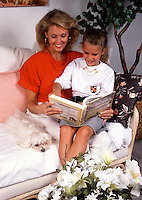 A smiling mother, young daughter and pet dog reading together.