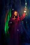 Artistic fairy tale portrait of a woman in a red hooded dress with a lantern in a forest at night with fireflies around and a tree trunk illuminated from the inside behind her. Witch or fairy. Halloween mysterious concept. Image © MaximImages, License at https://www.maximimages.com