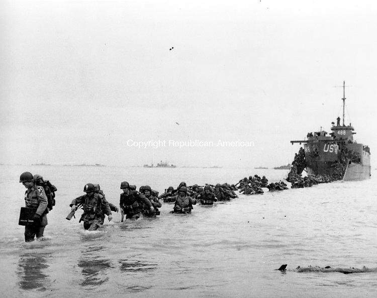 U.S. reinforcements wade through the surf from a landing craft in the days following D-Day and the Allied invasion of Nazi-occupied France at Normandy in June 1944 during World War II.  From the first sketchy German radio broadcast to the distribution of images filmed in color, it has taken decades for the full story of the D-Day invasion to come out. As world leaders and veterans prepare to mark the 70th anniversary of the invasion this week, multiple Twitter hashtags are following the ceremonies minute by minute. At the time, the reporting, filming and taking of photos was neither easy nor straightforward. Photographs by Robert Capa who was embedded with U.S. troops on Omaha Beach, took more than an week for his images to reach American news.   (AP Photo/Bert Brandt, File)