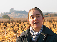 Gaelle Barrot owner of Chateau des Fines Roches in the vineyard in Chateauneuf-du-Pape, the village in the background, Vaucluse, Rhone, Provence, France