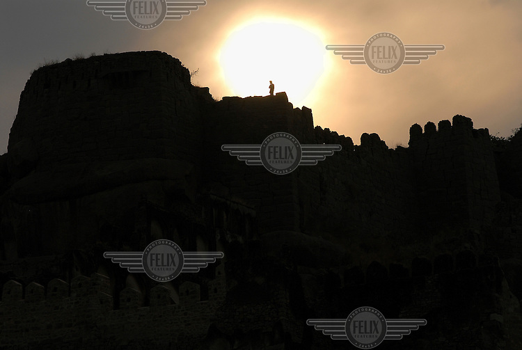 A figure stands silhouetted against the sunset on top of the ruins of the fortress at Golconda, a 16th Century Mughal city on the outskirts of modern Hyderabad...