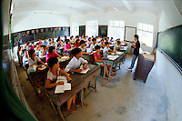 Barefooted students listen to instructor in a Chinese classroom. China.
