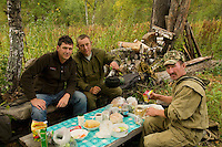 Eric Tourneret photographer and Sabit Galin, Aglam Ramujin, forest wardens, around a makeshift table in the camp.