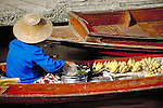 Female banana vendor in wooden barge at the Damnoen Saduak Floating Market