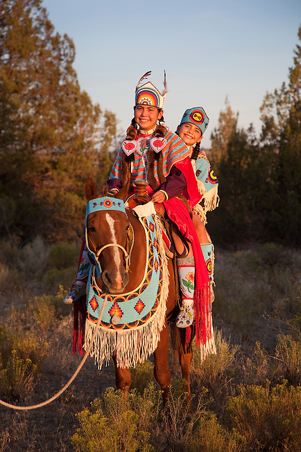 Native American family of two sisters dressed in traditional clothing and beadwork ride the family's decorated horse on the Warm Springs Indian Reservation, Oregon.