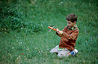 Young boy playing with a crossbow in a grassy field, Provence, France.