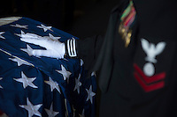 130513-N-DR144-627 PACIFIC OCEAN (May 13, 2013)- A Sailor holds the flag on the casket of a former service member during a burial at sea aboard San Antonio-class amphibious transport dock ship USS Anchorage (LPD 23).  Anchorage is underway after being commissioned in its namesake city of Anchorage, Alaska. (U.S. Navy photo by Mass Communication Specialist 1st Class James R. Evans / RELEASED)