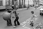 Young children playing safely outside in the street. Gladstone Street, Elephant and Castle,  south London SE1. England. 1975. The large ball with handles is a Spacehopper.