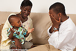 12 month old toddler boy with parents peek a boo game with father