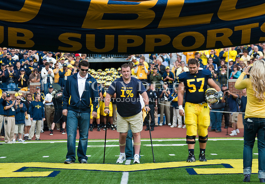 Brock Mealer, center, with brother and Michigan offensive lineman Elliott Mealer (57), leads the Michigan football team into Michigan Stadium, before an NCAA college football game with Connecticut, Saturday, Sept. 4, 2010, in Ann Arbor, Mich. Brock Mealer, who suffered a paralyzing car accident in 2008, credits the Michigan football program in aiding his recovery. (AP Photo/Tony Ding)