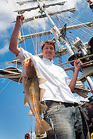 Galway, Ireland, July 2013. Fishing for cod on the way to Galway. It is the first time that Tallship Thalassa, a barquentine sailing vessel with 3 masts, sails from Belfast to Galway along the Irish coastline. While a full-rigged ship is square-rigged on all three masts, and the barque is square-rigged on the foremast and main, the barquentine extends the principle by making only the foremast square-rigged. The advantages of a smaller crew, good performance before the wind and the ability to sail relatively close to the wind while carrying plenty of cargo made it a popular rig at the end of the 19th century. Photo by Frits Meyst/Adventure4ver.com