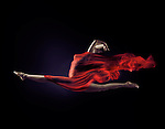 Surreal photograph of a woman with flowing red cloth that looks like a flame wrapping her nude body in a dynamic front split in mid-air isolated on black background Image © MaximImages, License at https://www.maximimages.com