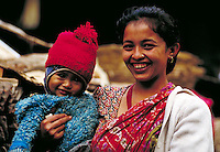 Proud smiling mother in sari holds bundled-up infant son; head and shoulders; full face. Kathmandu, Nepal.