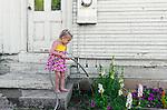 Toddler watering the flower garden, San Luis Obispo, California