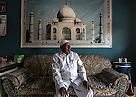 13 September, 2013, Ahmedabad, Gujarat INDIA : Travel agent Haji Ahmedbhai sits in front of a Taj Mahal poster in his small agency in Juhapura.   Juhapura was a small suburb with a small population until the mid 80s, but after the communal riots of Gujarat from 1985 until 2002, a large number of the Muslims migrated to Juhapura from the Muslim and Hindu-dominated areas of Ahmedabad.  Chief Minister of Gujarat , Narendra Modi has been announced as the Prime Ministerial candidate for the opposition BJP party in the Indian general elections slated for 2014.   Mr.Modi has been a controversial figure since his involvement in the 2002 Gujarat riots where a train full of Hindu pilgrims was attacked by Muslims returning from a disputed temple site in Ayodhya.  In retaliation some estimate up to 2000 Muslims lost their lives in communal violence.   Mr. Modi is alleged to have condoned the violence despite being cleared of any allegations by a Special Investigation Team (SIT) appointed by the Supreme Court of India. Picture by Graham Crouch/New York Times