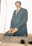 Marsh Arabs. Southern Iraq.  Marsh Arab man at side of road with huge portrait of Saddam Hussein. 1984