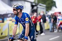 Mark Cavendish (GBR/Deceuninck - Quick Step) rolling past the podium where Mathieu Van der Poel is awarded the yellow jersey<br /> <br /> Stage 2 from Perros-Guirec to Mûr-de-Bretagne, Guerlédan (184km)<br /> 108th Tour de France 2021 (2.UWT)<br /> <br /> ©kramon